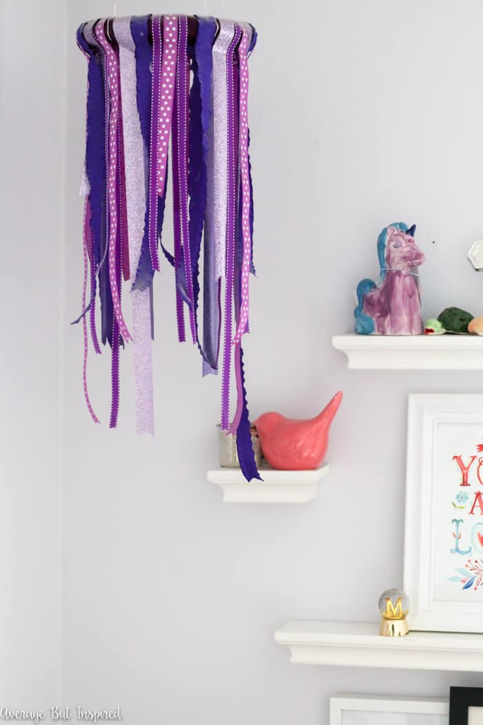 A DIY ribbon chandelier is an easy way to add a fun decorative touch to any room - especially a kids bedroom!  This DIY decor project only requires four supplies to make!  So easy.  #diyhomedecor #homedecorcrafts #ribbonchandelier