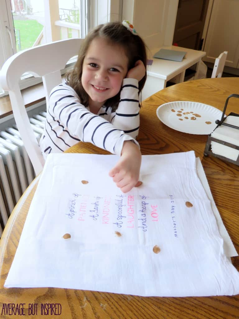 Turn kids' thumbprints into cookies on a cute tea towel.  It's the perfect gift for a mom or grandma who bakes!  Plus, the free downloadable quote can be used as a template for your own tea towel!