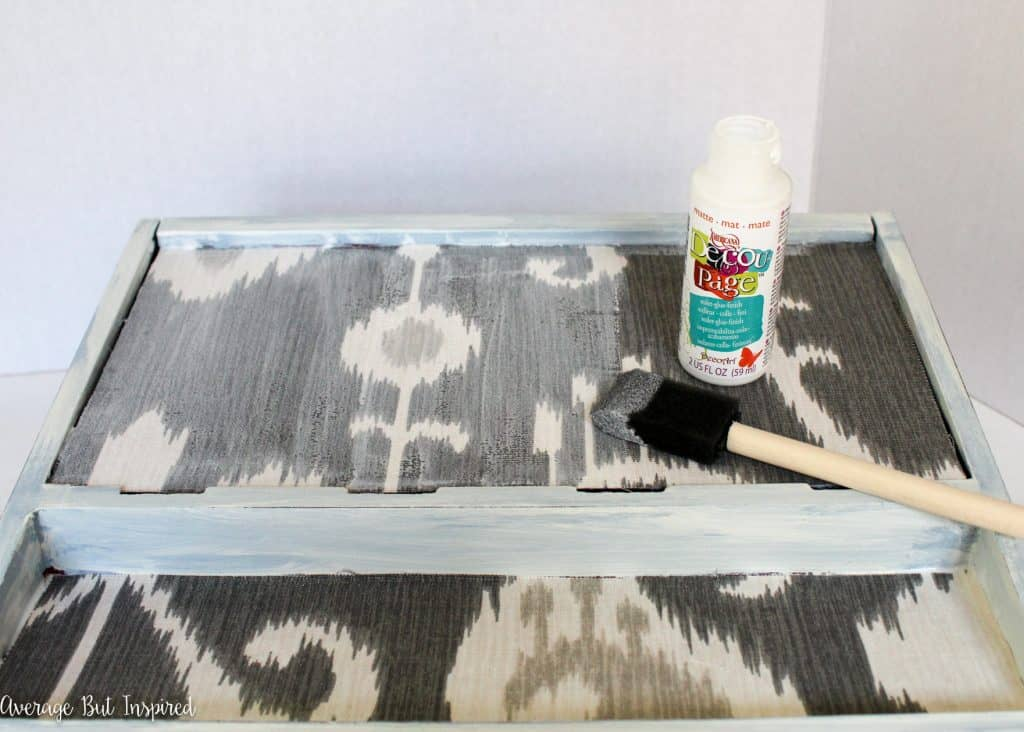 Keep phones and other technology organized with a pretty phone charger station! Learn how to give an old or thrifted one a makeover with fabric and paint in this easy tutorial!