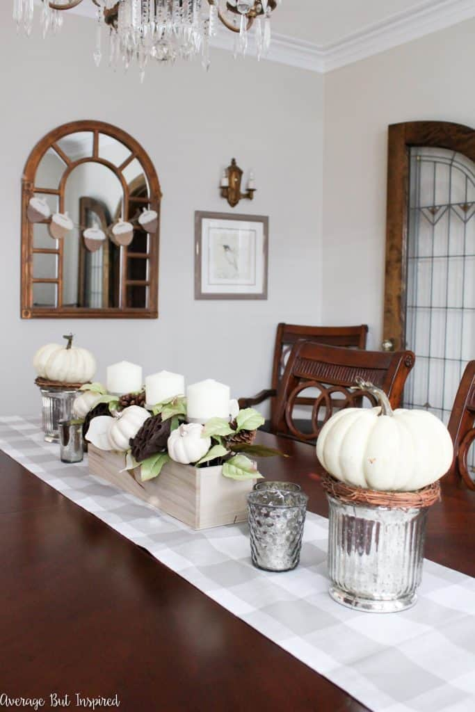This dining room is decorated for fall and autumn with shades of the season and lots of neutral tones. This fall centerpiece features white pumpkins and mercury glass for a sophisticated look.