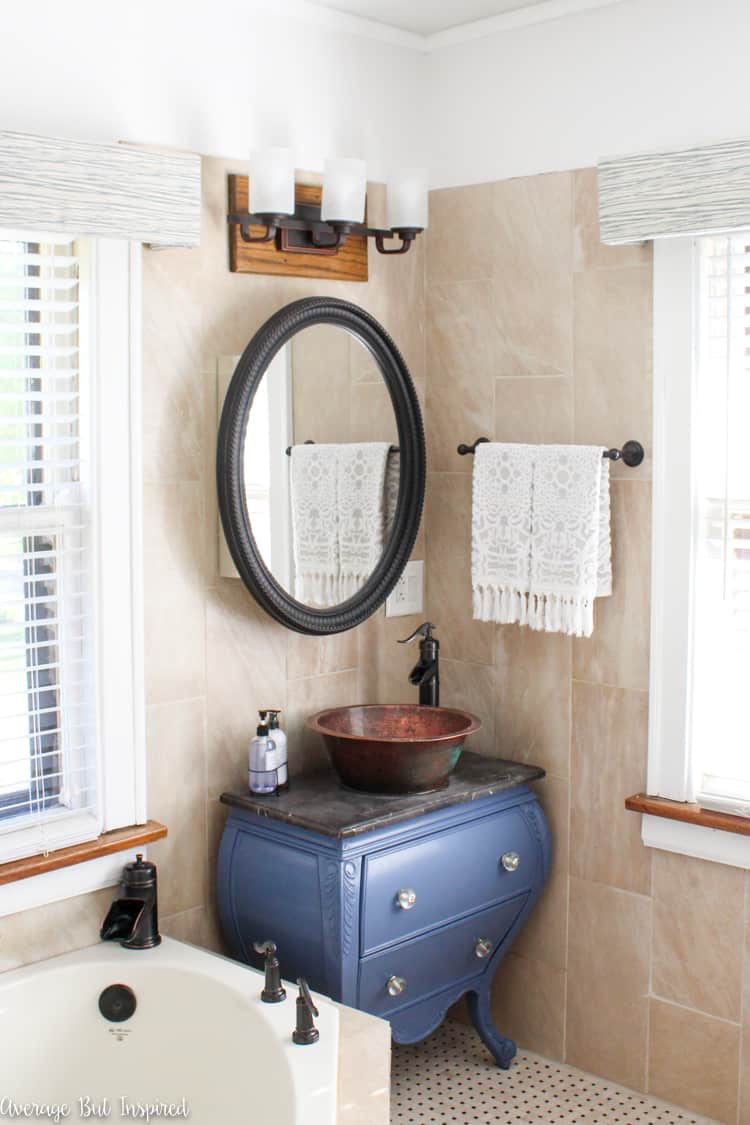 A dated master bathroom gets a light and bright makeover in tones of blue and gold. The painted blue vanity is a focal point. Click through to see all of the before and after photos!