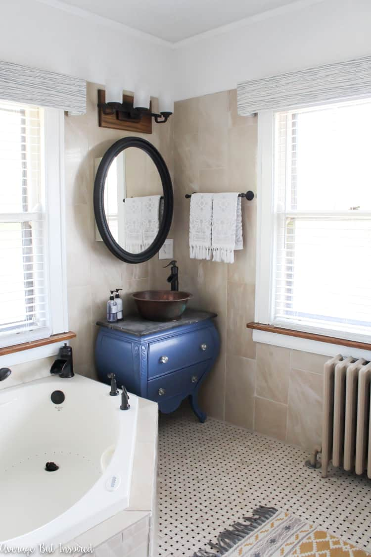 A dated master bathroom gets a light and bright makeover in tones of blue and gold. Click through to see all of the before and after photos!