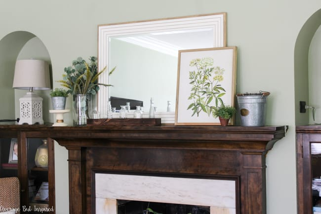 Check out this post to see beautiful summer mantel decorating ideas in shades of green and pulling elements from nature. Botanical prints, galvanized metal buckets, and a glass vase collection are some of the elements included.