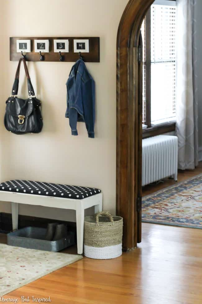 Love this small foyer decor! A pretty table, potted plant, and decorative accessories make it a functional and stylish space. The bench and wall hooks add to the functionality of this small entryway!