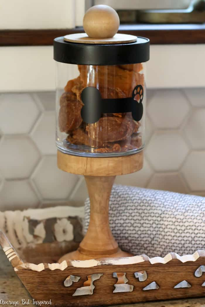 Transform a candle jar into an adorable DIY Dog Treat Container! This easy upcycle is a perfect place to store dog treats and will add a decorative touch to your kitchen!