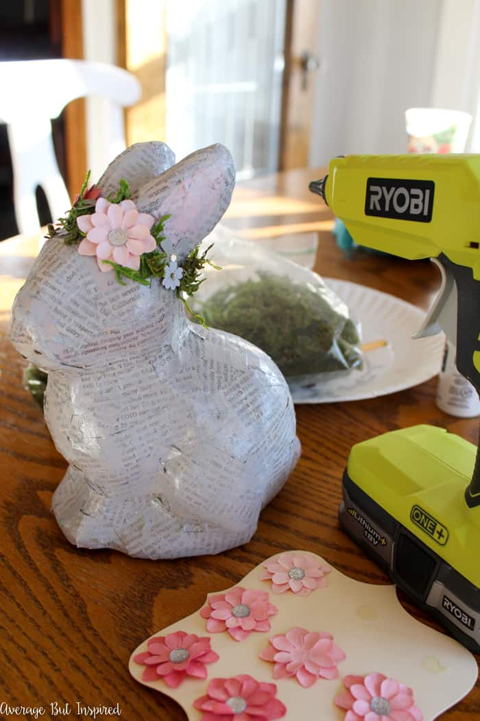 Transform an unfinished paper mache bunny into a charming and pretty vintage paper mache bunny with simple supplies like newspaper and paper flowers. This paper mache bunny will add such a pretty touch to your spring or Easter decor!