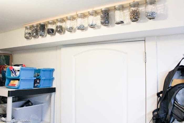 This is SO SMART! Take advantage of unused space on the ceiling or under a cabinet to create hanging mason jar storage! Use the mason jars to store and organize all kinds of small things - from tools to screws to craft supplies to spices! It couldn't be easier to create a hanging mason jar storage system in your home. This post shows you how!