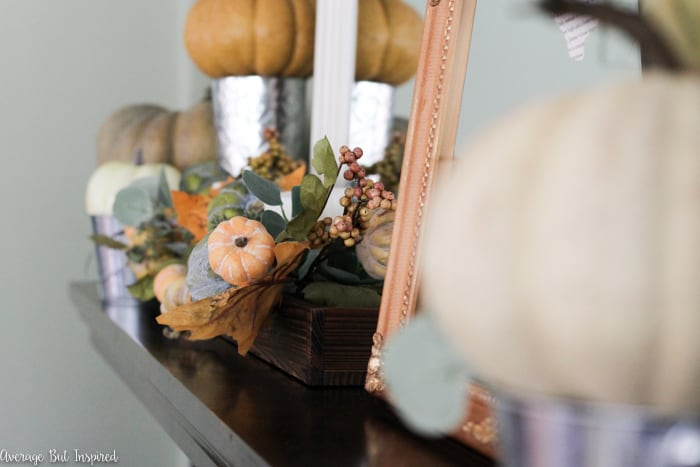 Beautiful! See how this blogger used inexpensive items like faux pumpkins, book pages, and acorns to create a pretty fall mantel in shades of green, orange, and white.