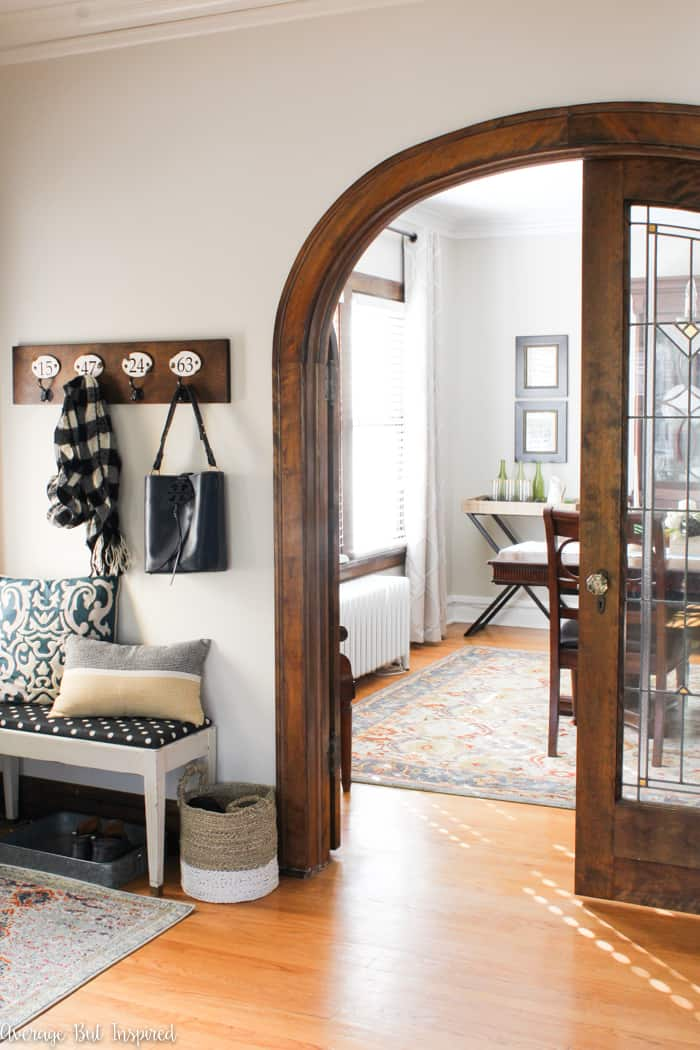 This welcoming foyer features a bench for putting on shoes and hooks for hanging jackets and bags. Get three awesome tips for budget redecorating in this post.