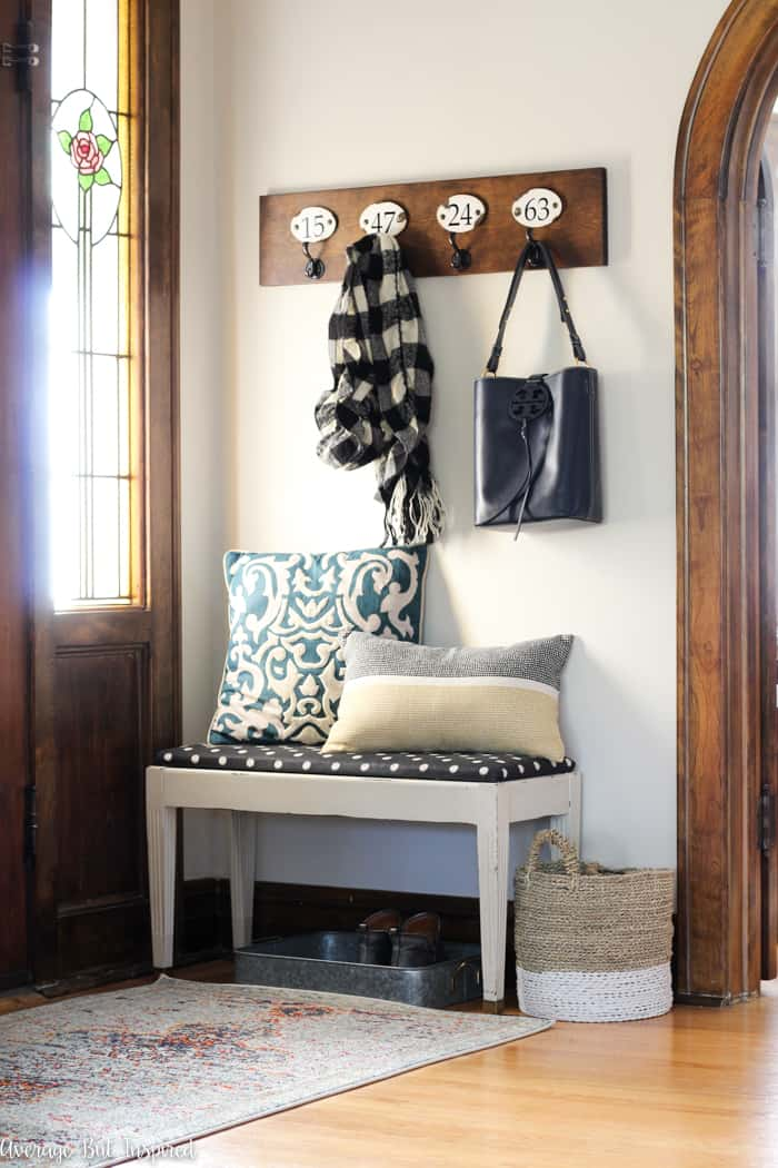 This small foyer is packed with functionality! Hooks and a bench give visitors a warm welcome. Plus, get three awesome tips for redecorating on a budget.