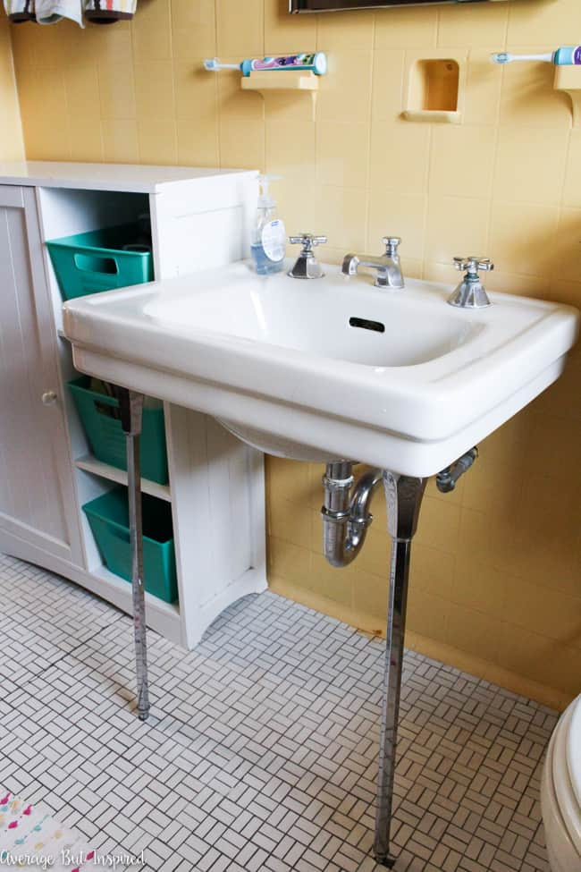 This vintage 1920s bathroom features an original sink on chrome console legs.