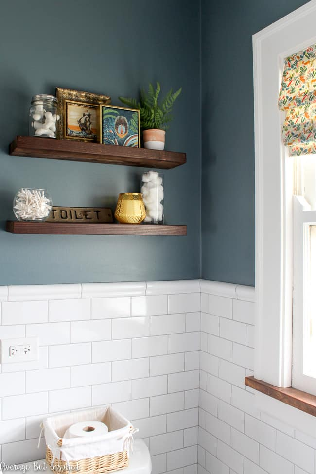 Floating shelves above the toilet are a place to display artwork, useful items for the bathroom like cotton swabs and cotton balls, and a nice candle. Wall color is Charlotte Slate by Benjamin Moore.