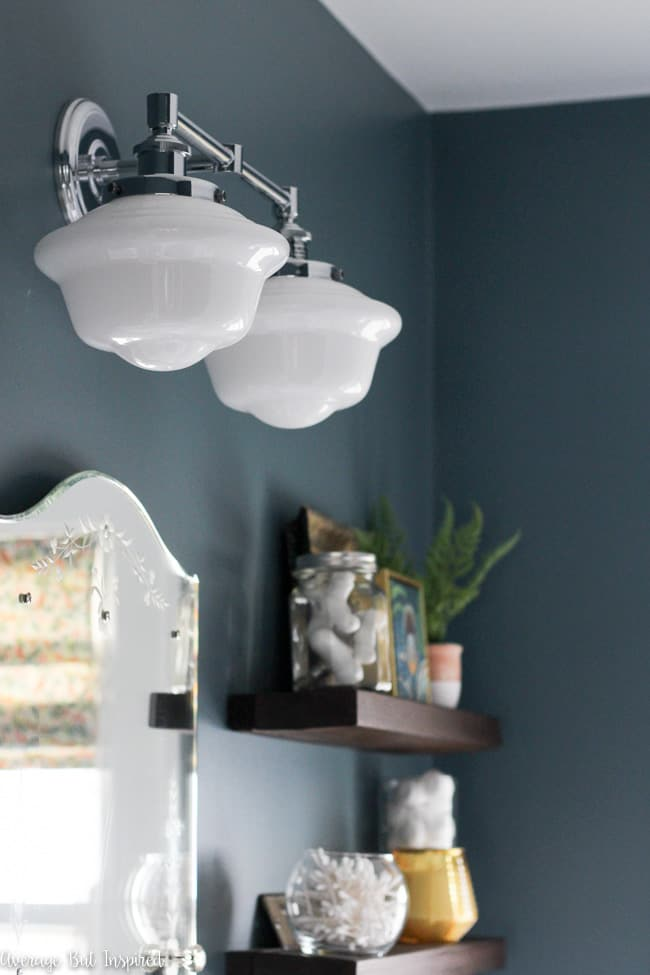 This vintage look milk glass schoolhouse bathroom sconce paired with moody blue paint (Charlotte Slate by Benjamin Moore) make a beautiful statement in a small bathroom.