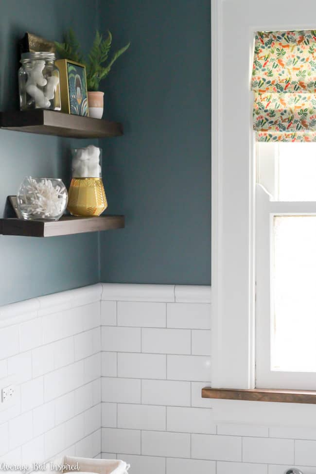 This bathroom features beautiful white subway tile with chair rail and light gray grout. Wall color is Charlotte Slate by Benjamin Moore.