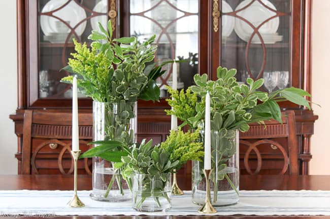 With around $10 of grocery store greenery, you can create a gorgeous centerpiece for your home or any event! Using different shades of foliage and a special trick, you'll make a greenery centerpiece that is beautiful and budget-friendly.