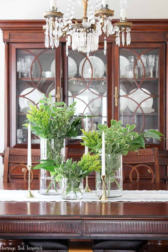 With around $10 of grocery store greenery and thrifted brass candlesticks, you can create a gorgeous centerpiece for your home or any event! Using different shades of foliage and a special trick, you'll make a greenery centerpiece that is beautiful and budget-friendly.