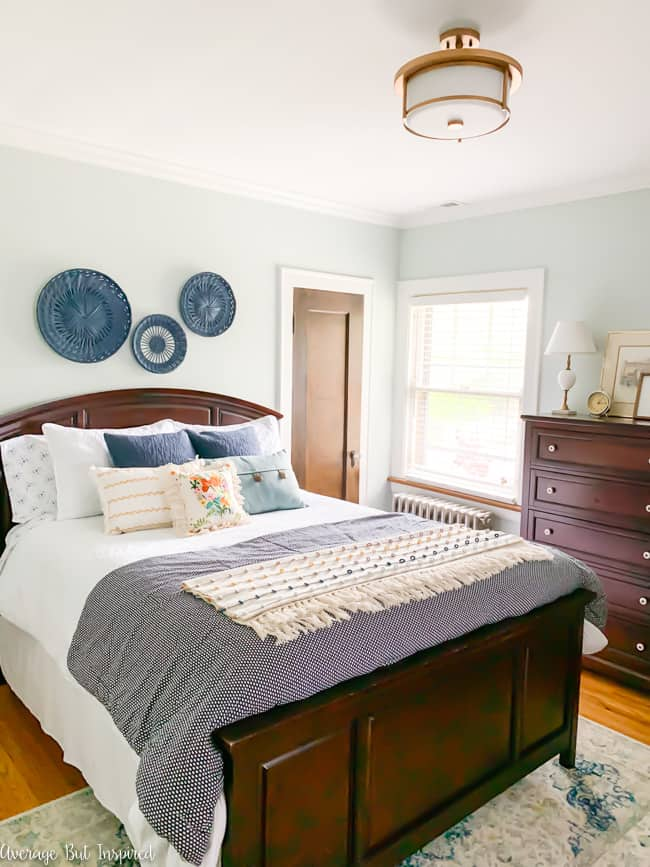 A trio of painted baskets used as wall art adds a pretty, cottage touch to this master bedroom.