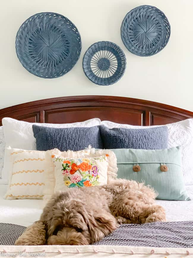 Chalk painted rattan baskets hanging on the wall are wonderful wall decor for over a bed. This budget-friendly project is super easy, too!