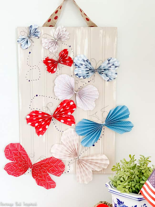 Make a cute Fourth of July sign with DIY paper butterflies. This unique piece of Fourth of July decor is so cute and easy to make!
