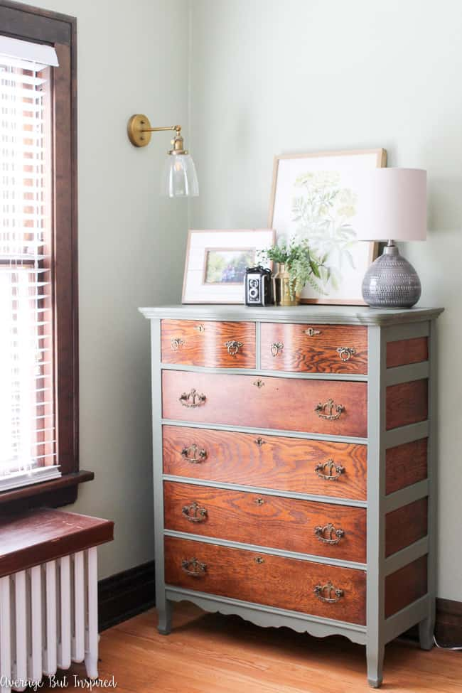 Gorgeous! This tall dresser looks right at home in this green living room. The two-tone look features natural wood and Cypress Vine green paint by Behr.