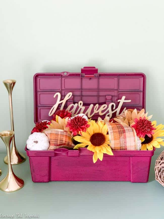 Love this pretty fall flower arrangement! See how she transformed a Dollar Tree toolbox and made it a beautiful fall planter!