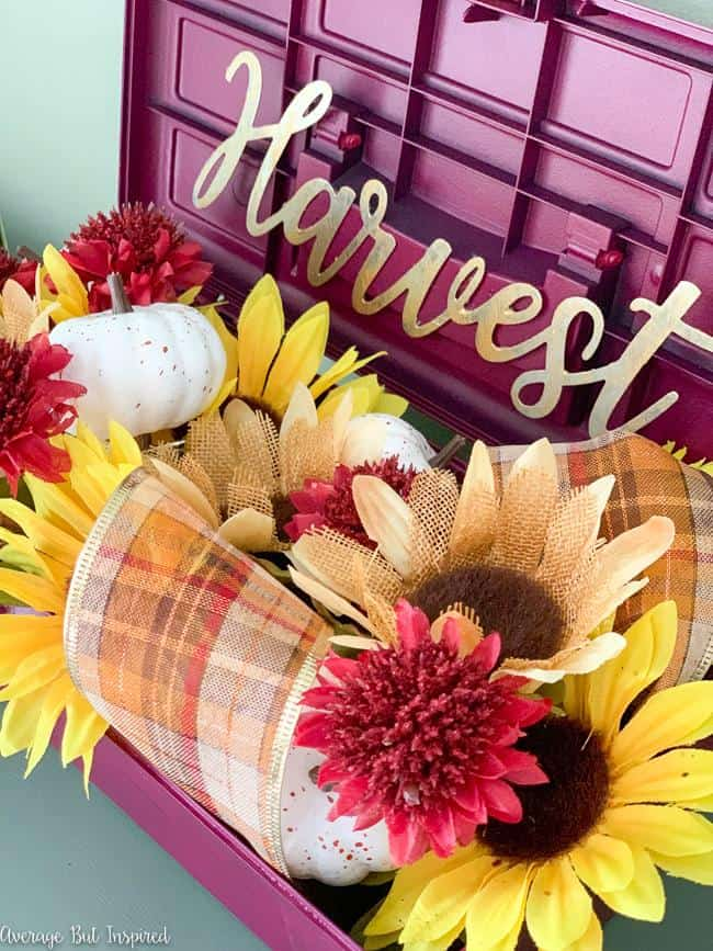 This is so pretty! Learn how to upcycle a toolbox into a planter! This fall arrangement is gorgeous and made entirely with Dollar Tree florals.