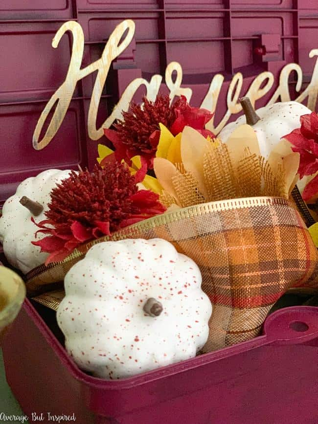 Faux pumpkins, plaid ribbon, and faux florals make a beautiful fall floral arrangement.