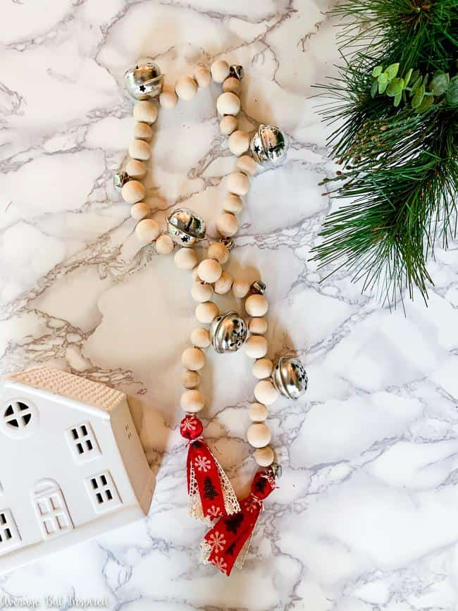 Make a pretty wood bead and jingle bell garland for Christmas! This DIY wood bead garland is so easy to make - click to view the tutorial on how to make your own!