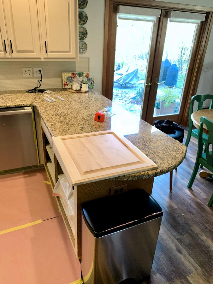 In order to convert a kitchen desk to pull-out trash, this blogger ordered a custom size cabinet door to fit the space.